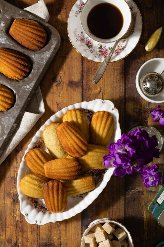 earl grey madeleines on a platter with a tea set and flowers
