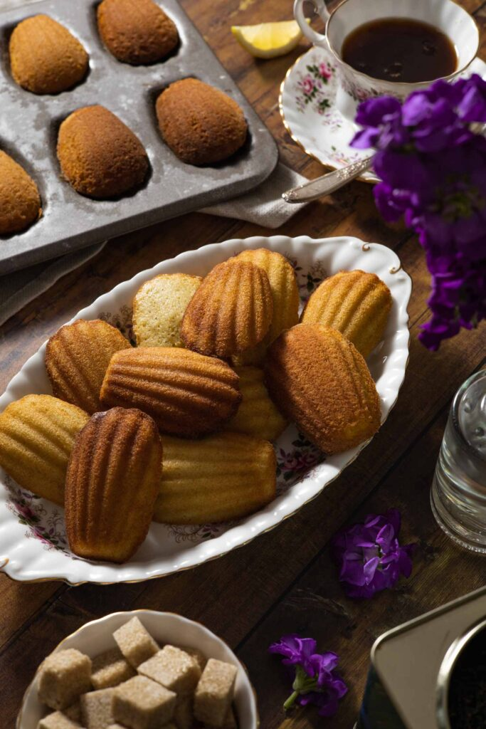 madeleins on a platter, a cup of earl grey tea, flowers in a vase, and a bowl of sugar cubes