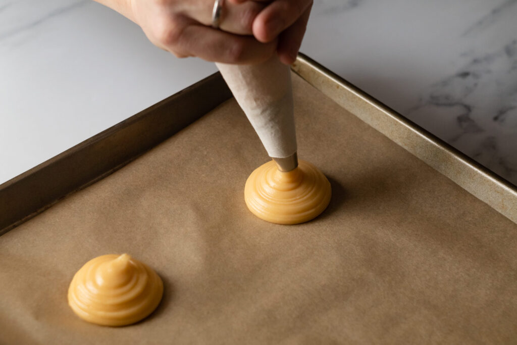 piping mounds of choux pastry for profiteroles