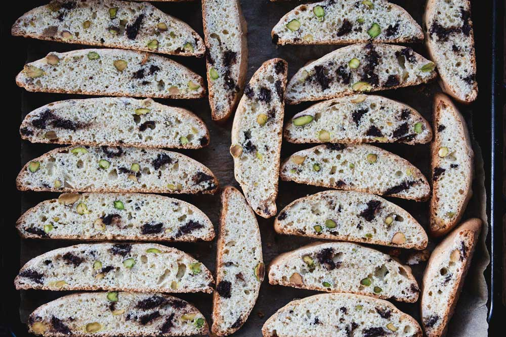 sliced biscotti on a parchment-lined baking tray