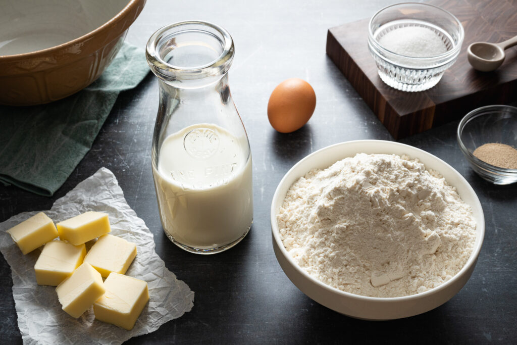 the ingredients to make Danish brunsviger cake: a bowl of flour, pads of butter on parchment paper, active dry yeast in a glass bowl, an egg, and granulated sugar in a ramekin