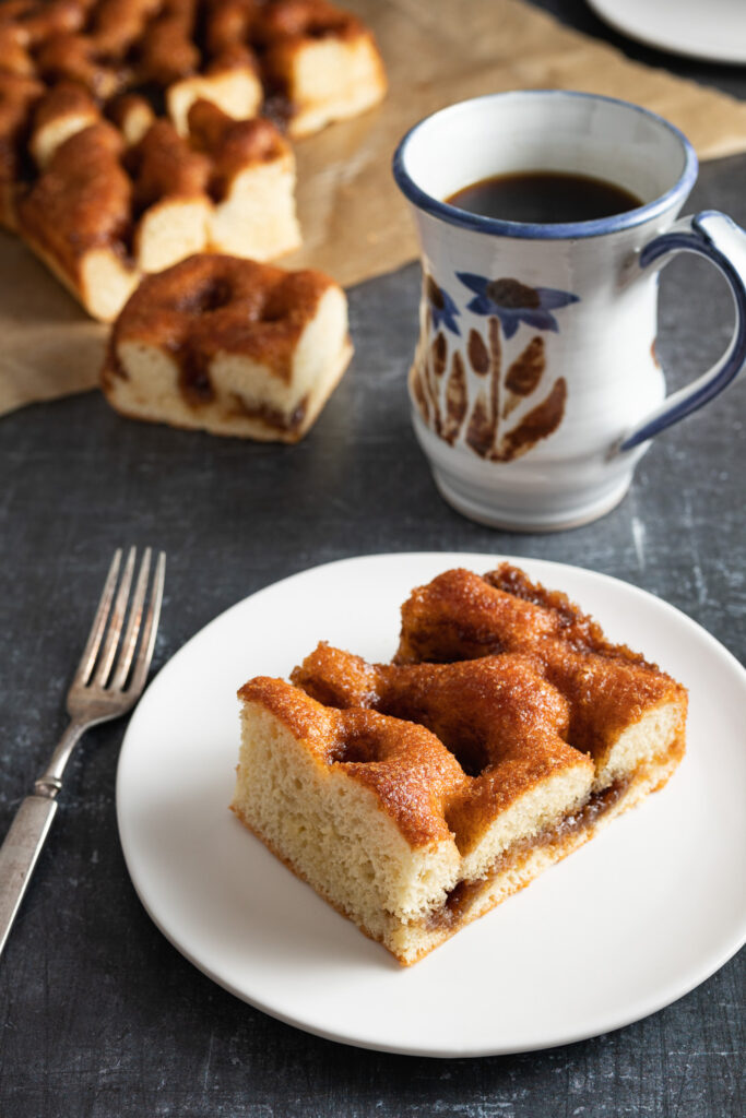 piece of brunsviger coffee cake on a white plate, antique fork, coffee mug with flowers painted on it, with cake in the background