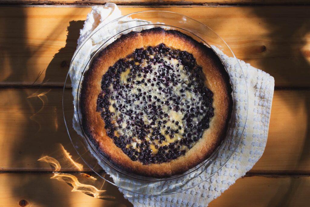 mustikkapiirakka blueberry tart on a wooden picnic table