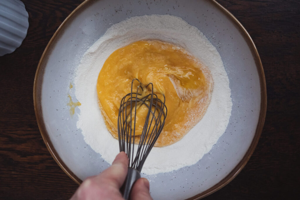 whisking the eggs into the flour in a mixing bowl