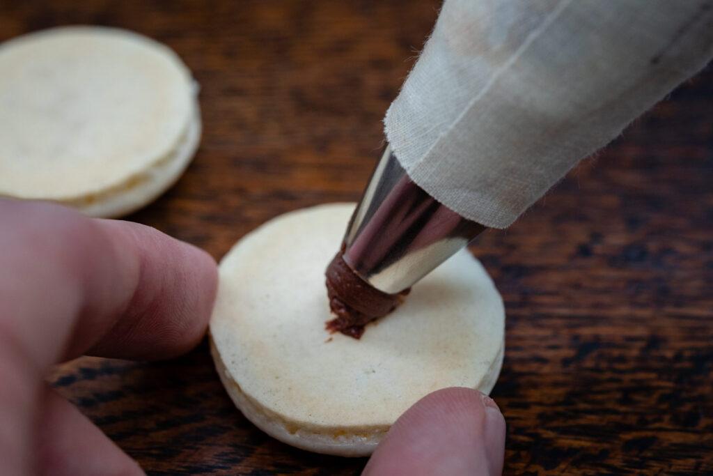 piping ganache on macarons