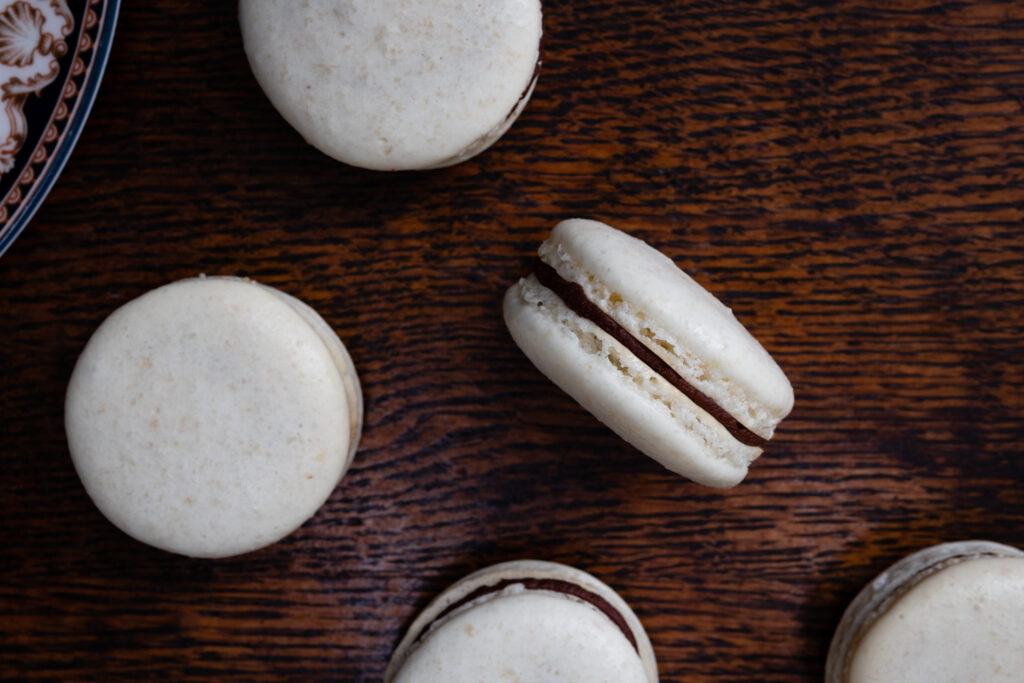 almond macarons filled with dark chocolate ganache on wooden table