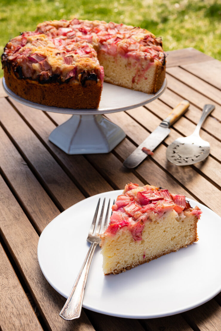 a slice of rhubarb cake on a white plate, rhubarb cake on a cake stand on a wooden table