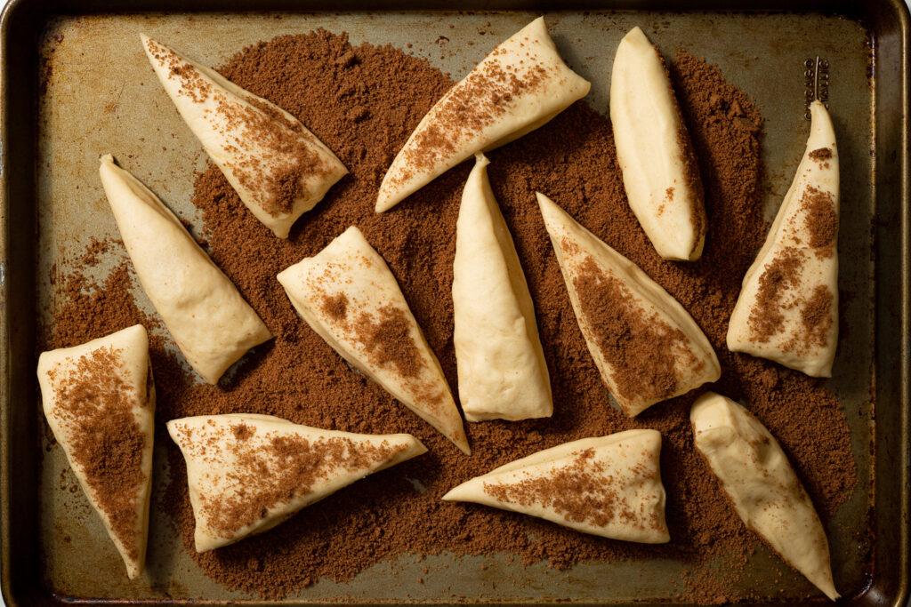 zeeuwse bolussen dough divided and sitting in cinnamon sugar mixture in a baking sheet