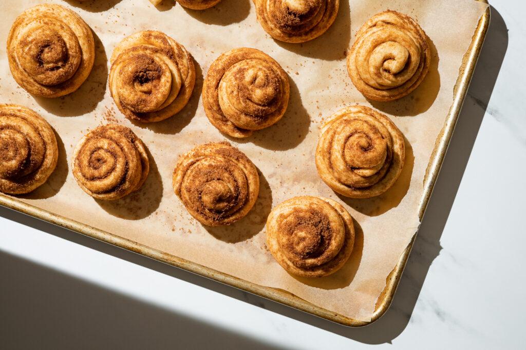 proofed zeeuwse bolussen cinnamon rolls on a parchment lined baking sheet