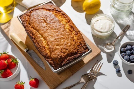 french yogurt loaf cake with strawberries, blueberries, yogurt pot, lemons, and silverware