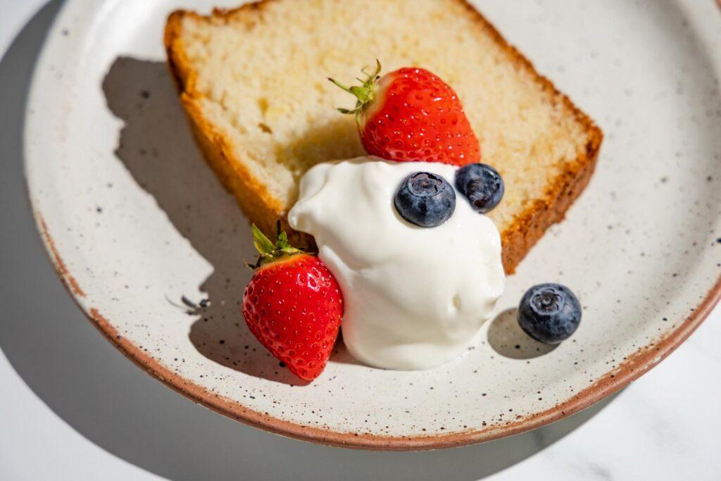 yogurt cake slice with a dollop of yogurt, strawberries, and blueberries